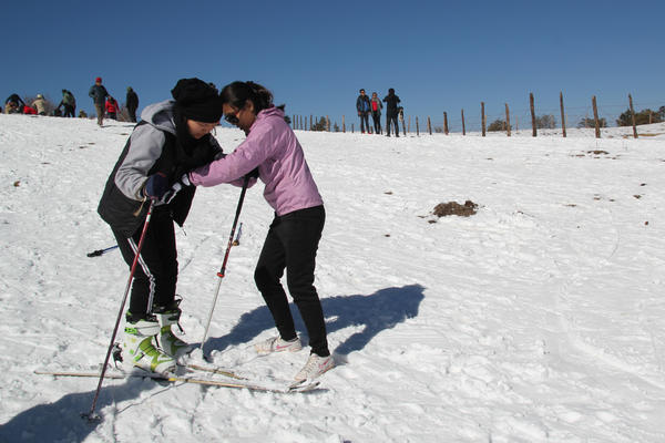 Fenchoke Sherpa (right), an instructor with the Nepal Ski and Snowboard Foundation, gives tips to Doma Hyolmo, 15, on her first attempt at skiing.