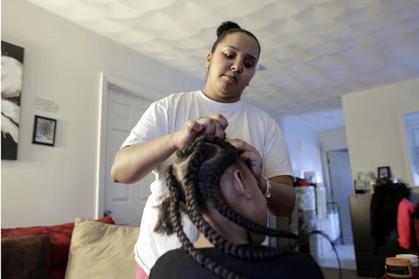 In this Sunday, Feb. 19, 2017 photo Jocelyn DoCouto, top, adds braid extensions for seven-year-old Zanyrah Parrott, of Pawtucket, R.I., in DoCouto's home, in Pawtucket. The billionaire industrialist Charles Koch might not have a lot in common with DoCouto, but they are both part of a national movement to deregulate the business of African-style braiding. DoCouto is pushing for state legislation in Rhode Island that would exempt her from the cumbersome and expensive occupational licensing requirements for hairdressers and barbers. (AP Photo/Steven Senne)