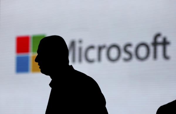 An unidentified man walks in front of the Microsoft logo at an event in New Delhi. Microsoft is at the center of a Supreme Court case on whether it has to turn over emails stored overseas.
