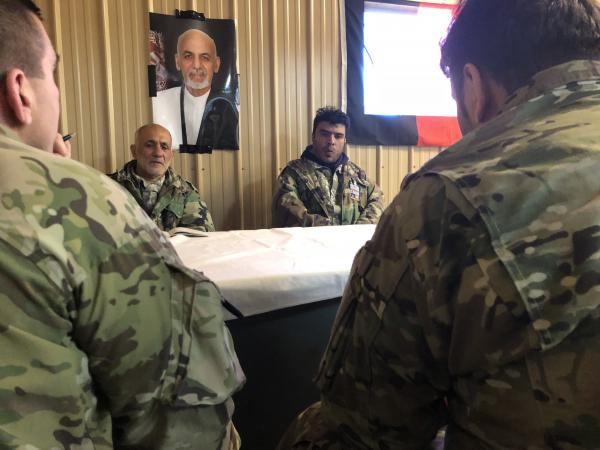 Maj. Jason Moncuse, back to camera on left, meets with actors portraying Afghan village officials. The training exercise at Fort Polk, La., is preparing the 1st Security Force Assistance Brigade for a spring deployment to Afghanistan.