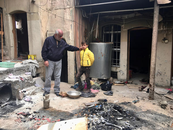 Ziad Abdul Qader and his son Mohammad, 11, came back to their damaged home in the Mosul's Old City. They found ISIS fighters' corpses inside. Abdul Qader owned a clothing store before ISIS. He says Mohammad has panic attacks and has forgotten how to read and write.