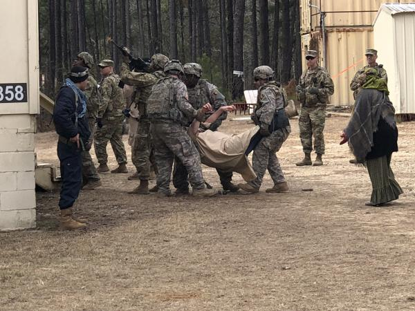 Troops in a training exercise with actors portraying Afghan villagers respond to a mock ambush. The Army unit is training to serve as advisers ahead of a spring deployment to Afghanistan.