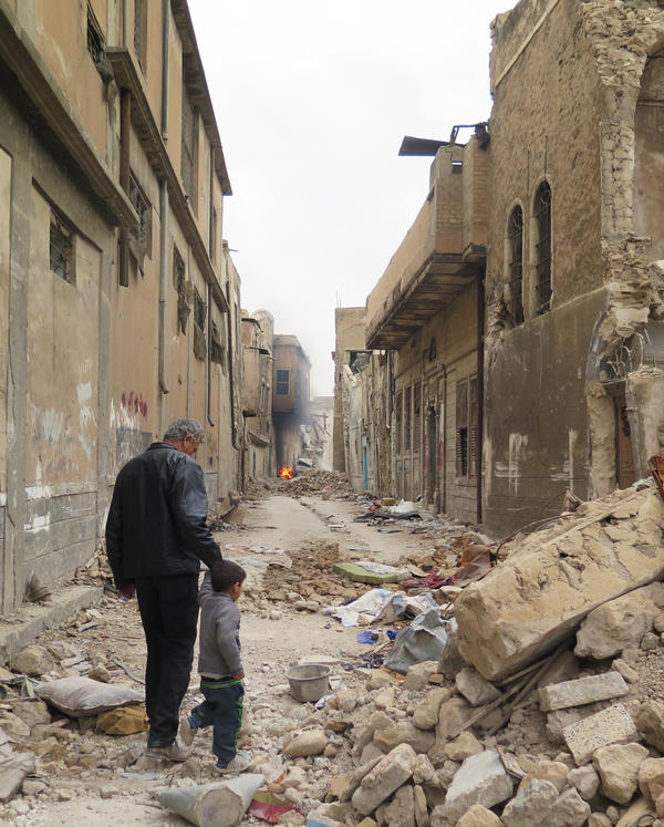 Amer Mohammad walks with his son Yasser, 4, in Mosul. Mohammad is a health ministry employee who hasn't been paid in almost four years. His 15-year-old son Ahmed was killed in a mortar attack in the old city.