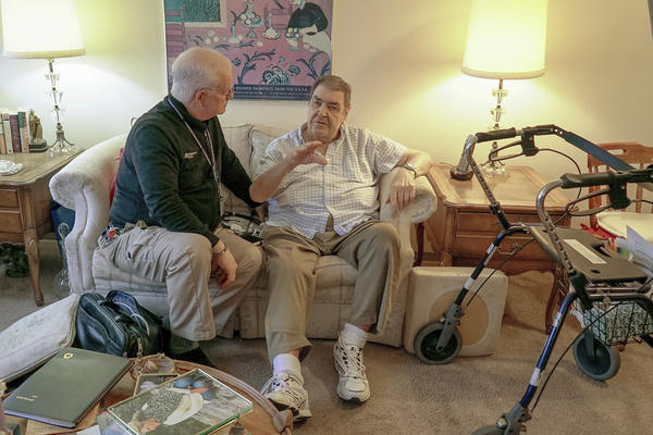 Nurse practitioner Dwayne Dobschuetz, left, visits patient Marvin Shimp, at Shimp's home in Chicago on Jan. 10, 2018. Shimp has lost much of his vision to macular degeneration and Dobschuetz's house calls help him stay out of the hospital with regular visits to check vitals and answer questions. Dobschuetz sees several patients in their homes each day, traveling by bicycle. He works at Northwestern Medicine in Chicago, which is taking a new approach to helping older patients stay healthier. (AP Photo/Teresa Crawford)