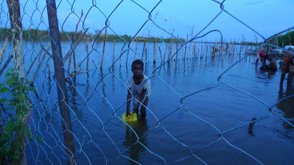 A child collects water inside a makeshift chain-link enclosure.