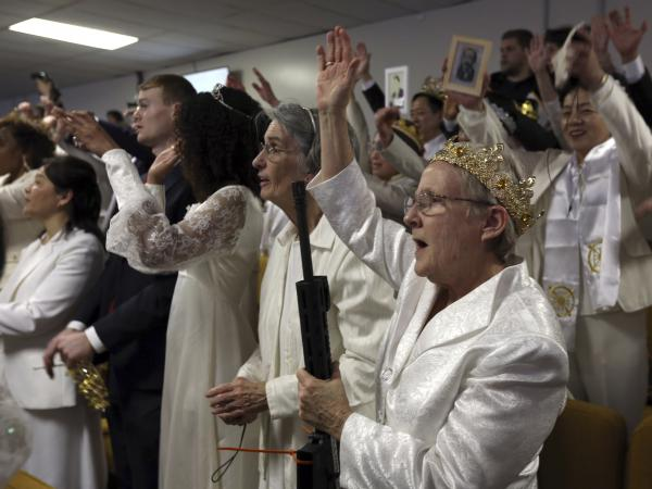 A woman wears a crown and holds an unloaded weapon during services at the World Peace and Unification Sanctuary, on Wednesday in Newfoundland, Pa.