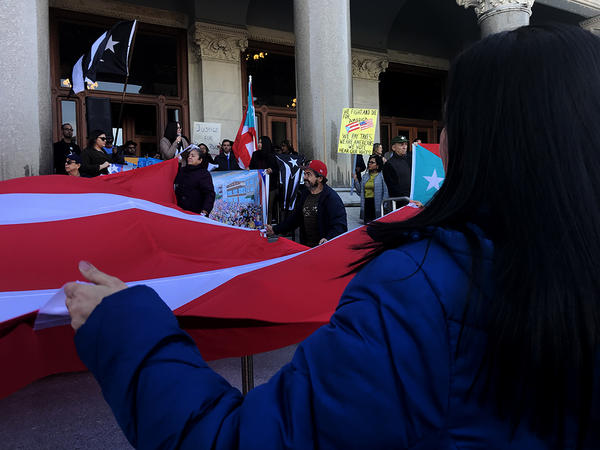 This woman is one of 14 people holding a Puerto Rican flag while listening to community organizers call for disaster relief on the steps of the Capitol in Hartford.