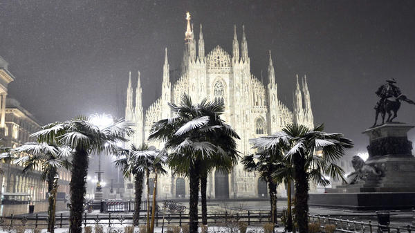 Palm trees dusted with snow stand in front of the Milan Cathedral during a snowstorm early Thursday, as much of Europe is hit by a Siberian cold snap.