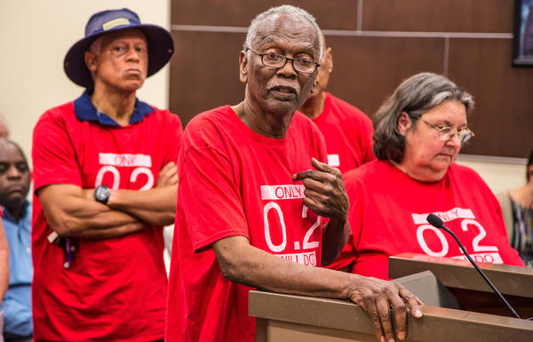 Robert Taylor, center, speaks at a St. John the Baptist Parish council meeting in 2017. He and the other members of the citizens' group around him wear T-shirts that reference the safety limit for the chemical chloroprene.