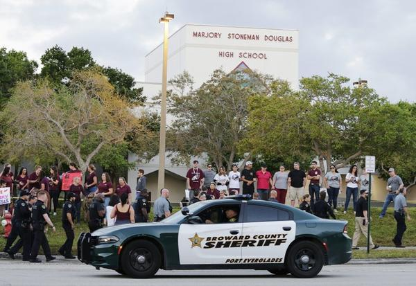 In this Feb. 28, 2018 photo, a police car drives by Marjory Stoneman Douglas High School in Parkland, Fla., as students returned to class for the first time since a former student opened fire there with an assault weapon.
