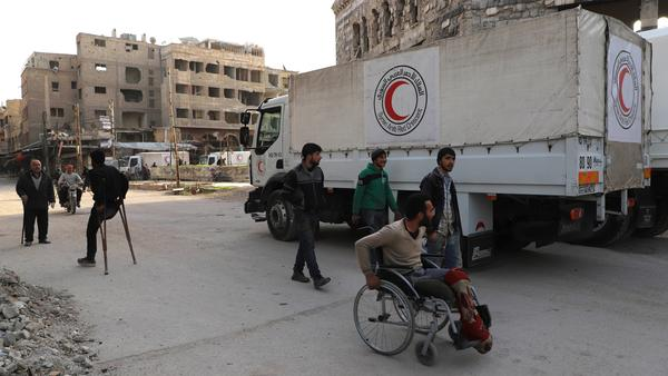A convoy of Syrian Red Crescent trucks arrives in Douma, in the Syrian rebel-held enclave of Eastern Ghouta, on Monday. This aid convoy is the first to reach the besieged area in weeks.