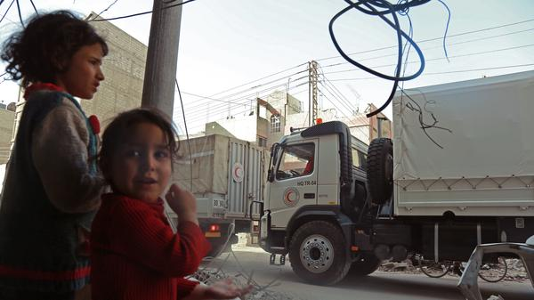 A convoy of Syrian Red Crescent trucks arrives in Douma, in Eastern Ghouta, on Monday. The convoy contained food aid for tens of thousands of people, but many medical supplies were blocked by the Syrian regime.