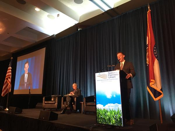 Jason Kander begins his address to the National Farmers Union conference on Monday in Kansas City. To his left is NFU President Roger Johnson.