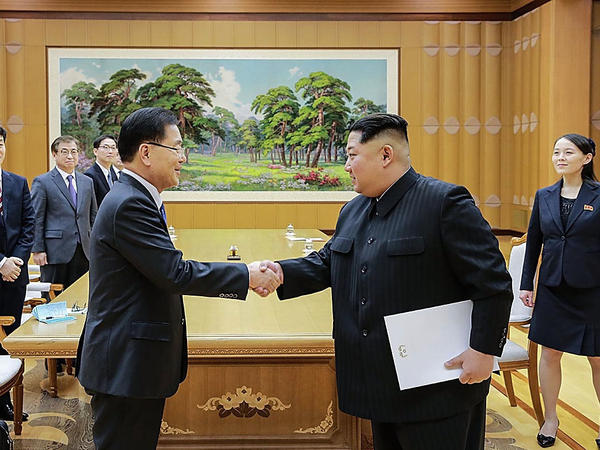 In this handout image provided by the South Korean Presidential Blue House, Chung Eui-yong (left), head of the presidential National Security Office, shakes hands with North Korean leader Kim Jong Un during their meeting on Monday in Pyongyang.