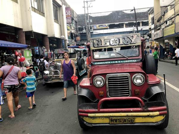 """A jeepney crowned with the name """"Morning Glory"""" navigates a Manila street during rush hour. Many jeepneys reach areas of the city where other public transit does not go."""