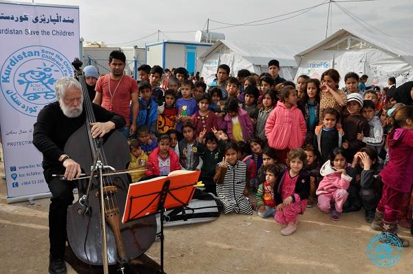 Dobbs playing for people at a Syrian refugee camp.