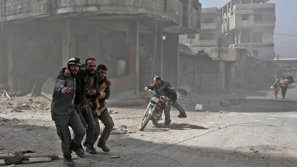 Volunteers from the Syrian Civil Defense help a man in Hamouria during shelling on rebel-held areas in eastern Ghouta on Tuesday. Heavy air strikes and clashes shook the Syrian rebel enclave as France and Britain called for an emergency U.N. Security Council meeting on the escalating violence.