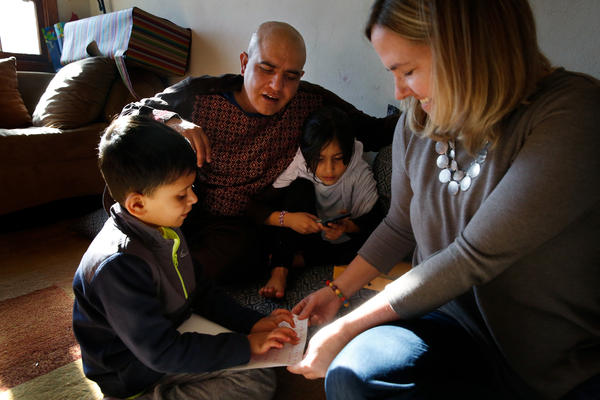 Cathy Meaney (right), a volunteer with International Neighbors, sits with Rahim Nishat and two of his children in the Nishats' apartment in Charlottesville, Va. The Nishat family is from Afghanistan.