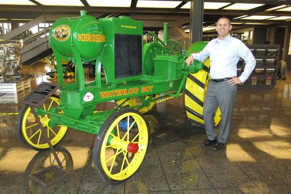 Neil Dahlstrom stands next to a restored Waterloo Boy tractor at World Headquarters, Moline, IL.
