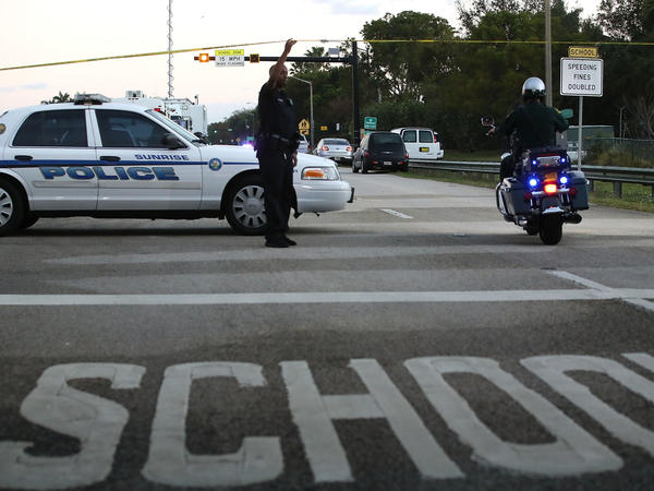Police secure a road near the Marjory Stoneman Douglas High School where 17 people were killed by a gunman, who legally passed a background check. The tragedy has intensified debate over how to improve the background check system in the U.S.