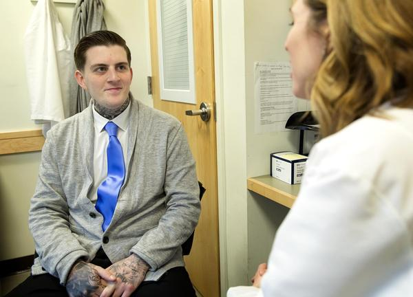 Patient Ricky Scimeca talks with Dr. Laura Kehoe at MGH's Bridge Clinic. (Robin Lubbock/WBUR)
