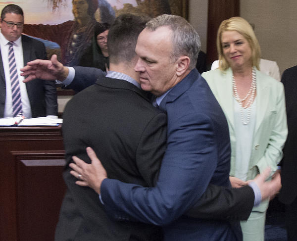 Florida Speaker of the House Richard Corcoran (center) hugs Hunter Pollack, whose sister was one of the 17 people killed last month in a mass shooting at a South Florida high school. The state House on Wednesday passed a package of measures intended to prevent another school shooting, sending the bill to the governor for his approval.