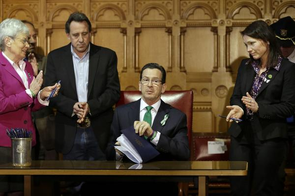 Connecticut Gov. Dannel Malloy, center, completes signing legislation that includes new restrictions on weapons and large capacity ammunition magazines, on April 4, 2013. Malloy is applauded by relatives of victims of the Sandy Hook shooting. (Steven Senne/AP)