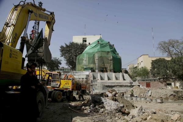 Heavy machinery works near the shrine of Mauj Darya, covered in protective green fabric. A concrete wall reinforcing the foundations is visible below the shrine.