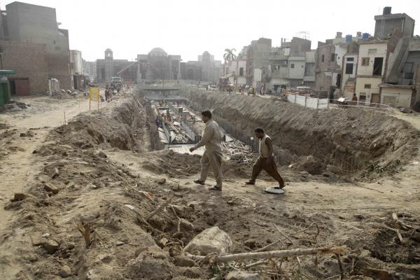 Men walk past the trench to accommodate the metro near the shrine of Mauj Darya. Activists against the train's route said they were particularly aggrieved by the trench-digging method. They say by clearing the dense urban fabric, the government razed hundreds of homes, displaced families and put the heritage sites at risk.