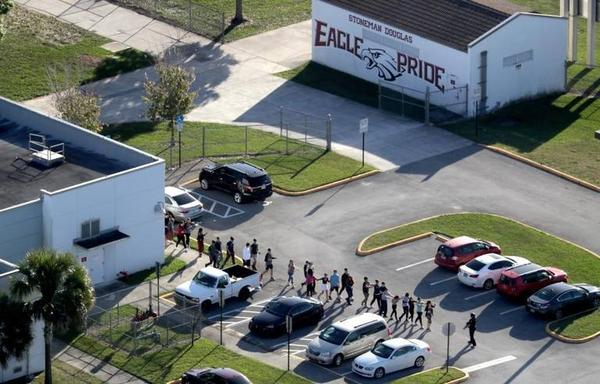 Students are evacuated by police from Marjorie Stoneman Douglas High School in Parkland on Feb. 14 after a shooter opened fire on the campus on Feb. 14.