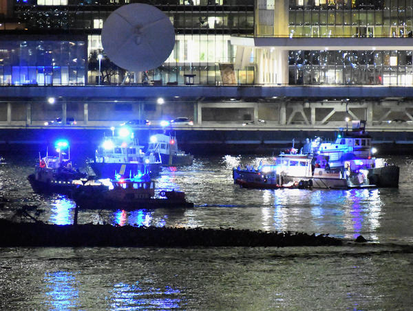 Police and firefighters respond to a helicopter crash into New York City's East River on Sunday evening.