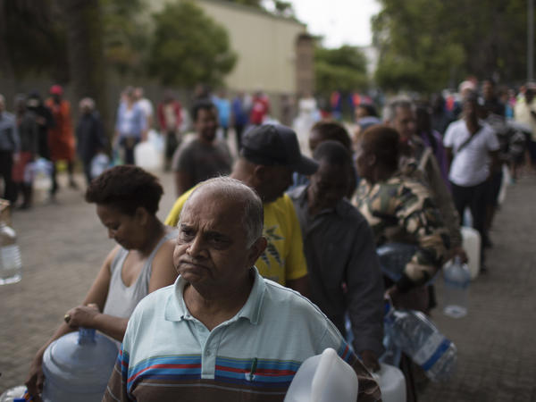 Residents wait to fill containers at a source for natural spring water in Cape Town.