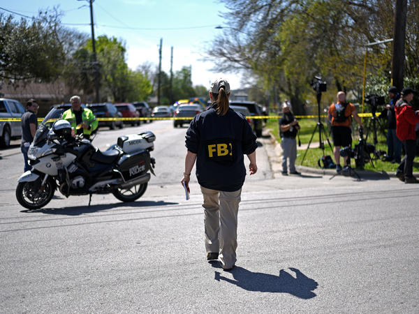 An FBI agent walks toward the scene of one of the blasts in Austin on Monday.