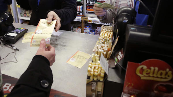 Cashiers in Merrimack, N.H., sell a lottery ticket at Reeds Ferry Market convenience store in January. A woman who bought the winning ticket there won the $559.7 million jackpot and now has won the right to remain anonymous.