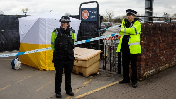 Police officers stand guard by a forensics tent in a Sainsbury's parking lot on Tuesday, as investigations continue more than a week after the poisoning of Sergei Skripal and his daughter in Salisbury, England.
