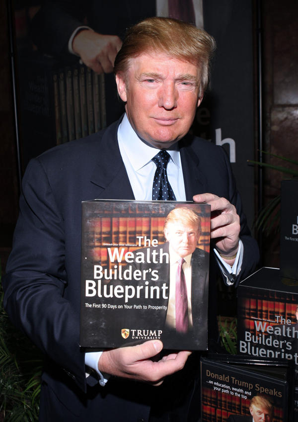 Donald Trump holds a book at a press conference announcing the establishment of Trump University in 2005.