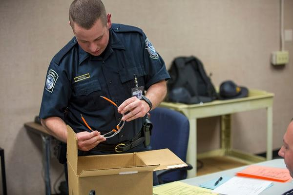 U.S. Customs and Border Protection trainee Patrick Provost examines a pair of sunglasses from a box during his manifest testing. (Jesse Costa/WBUR)
