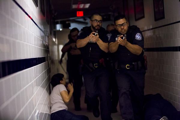 Two CBP trainees walk past a woman on the floor as they look to apprehend an active shooter during a drill. (Jesse Costa/WBUR)