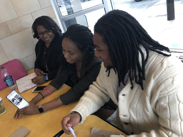 Ifeolu Claytor, 23, (right) and Gabrielle Jackson, 28, (far left) check out a social media voting video on Esosa Osa's phone. All three are members of the Northeast Ohio Young Black Democrats.