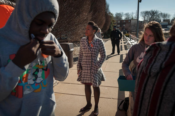 Maplewood Richmond Heights Superintendent Karen Hall watches as students leave school to demonstrate to honor victims of the Parkland school shooting.