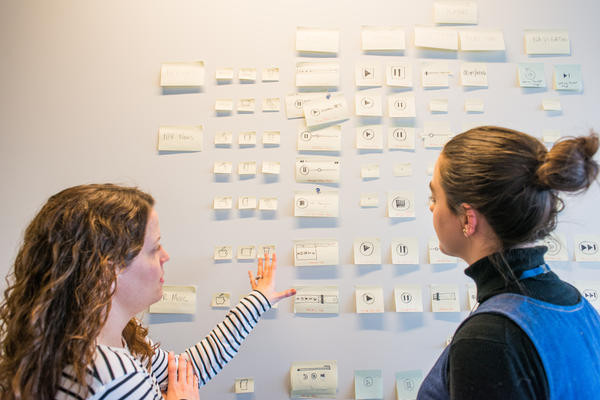 Libby and Katie discuss in front of Veronica's sticky notes near the NPR Music green room.
