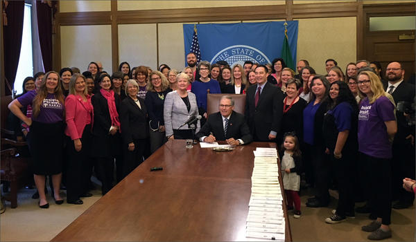Washington Gov. Jay Inslee poses with state Sen. Karen Keiser at a bill signing ceremony on Wednesday.