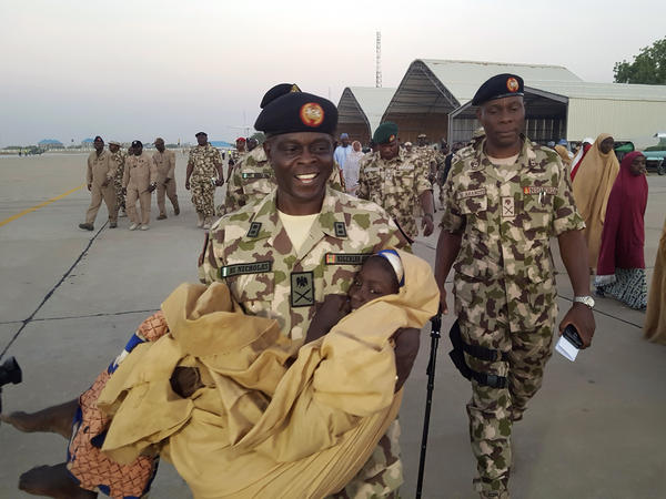 Maj. Gen. Rogers Nicholas, Theatre Commander, carries one of the freed students during a handover to government officials in Maiduguri on Wednesday.