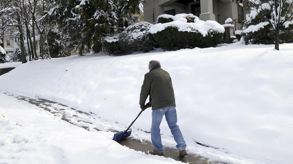 Mark Goldstein shovels the sidewalk in front of his house in Leonia, N.J., Thursday, after a spring nor'easter dumped up to a foot or more of snow across the region.