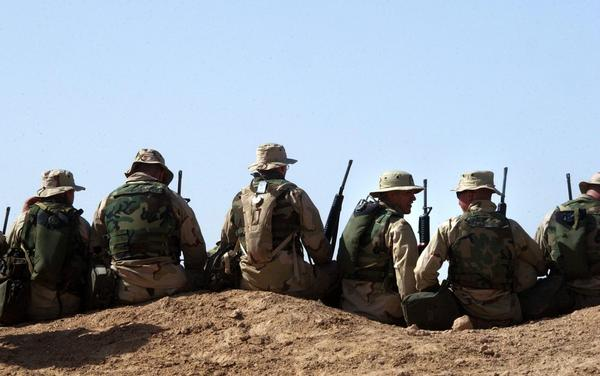 A group of U.S. Marines sit along the top of a dirt hill to listen to a Feb. 5, 2003 address by the Commandant of the U.S. Marine Corps, Gen. Michael Hagee, at a Marine support camp near the Iraqi border in northern Kuwait. (Scott Nelson/Getty Images)