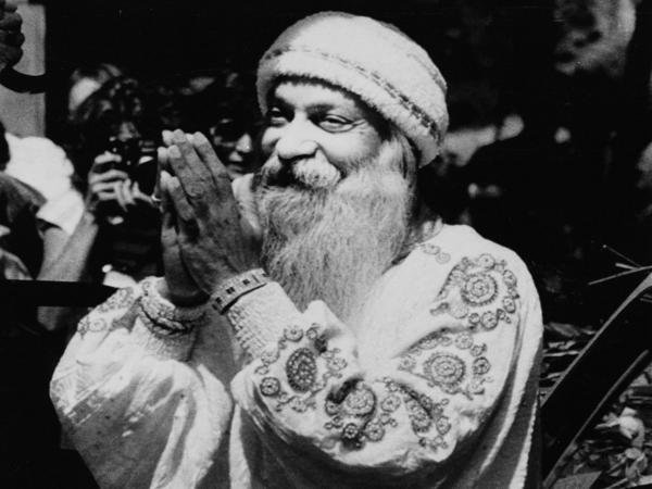 Bhagwan Shree Rajneesh greets his followers, the Rajneeshees, during a daily afternoon drive-by in one of his Rolls-Royce cars in Rajneeshpuram, Ore., on Aug. 18, 1984.
