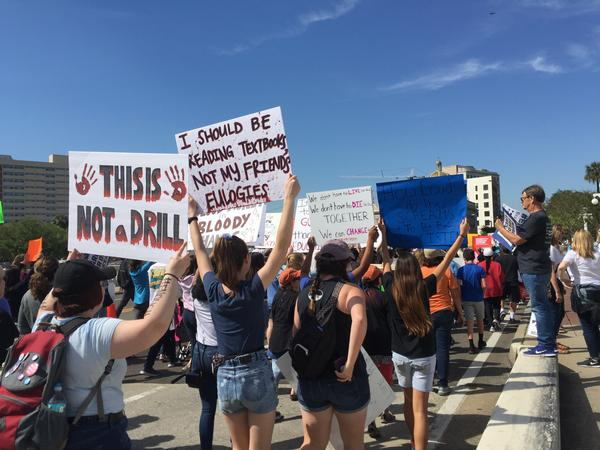 Attendees march more than a mile in downtown Tampa, holding signs that ask for gun control.