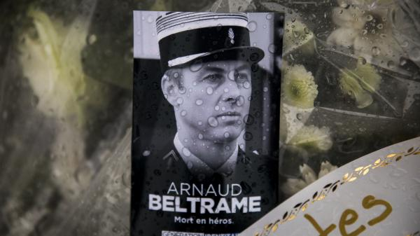 A photo of Lt. Col. Arnaud Beltrame rests on a bunch of flowers at the main gate of the police headquarters in Carcassonne, France. On Sunday, a man was arrested on charges of apologizing for terrorism after seemingly praising Beltrame's death on social media.