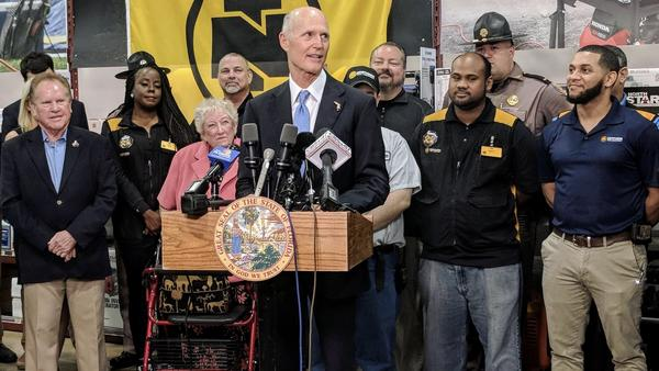 Scott flanked by Northern Tool and Equipment employees during his budget proposal announcement in Jacksonville in November 2017.