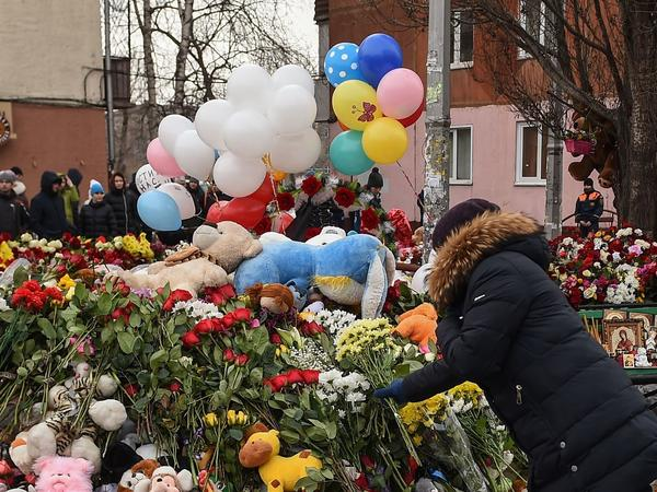"""People lay flowers at a makeshift memorial in tribute to the victims of a fire at a shopping centre in Kemerovo, Russia on Tuesday. Russian authorities denounced what they called """"flagrant violations"""" of safety norms that led to the deaths of 64 people, many of them children, in a fire at a busy shopping mall in an industrial city in Siberia."""